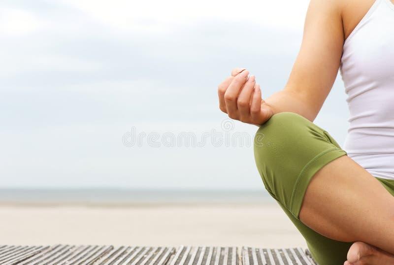 Stående av kvinnliga yogahänder på stranden royaltyfria bilder