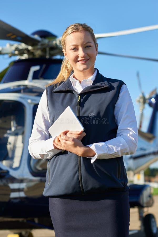 Stående av kvinnligpiloten Standing In Front Of Helicopter With Di arkivbilder