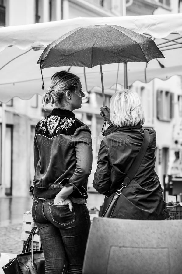 Stående av kvinnor som står med paraplyet på kullerstenställe i staden royaltyfri bild