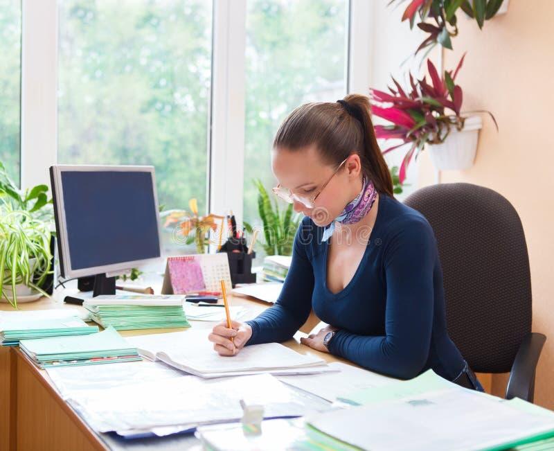 Stående av lärarekvinnan som arbetar i klassrum arkivbild