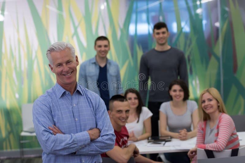 Stående av läraren med studentgruppen i bakgrund royaltyfri bild