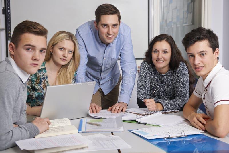 Stående av läraren And Pupils Working i klassrum tillsammans arkivfoton