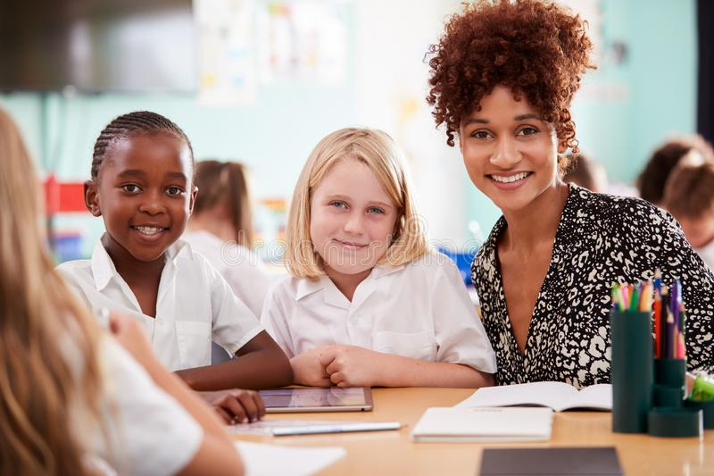 Stående av lärarinnaWith Elementary School elever som bär likformign genom att använda den Digital minnestavlan royaltyfria foton
