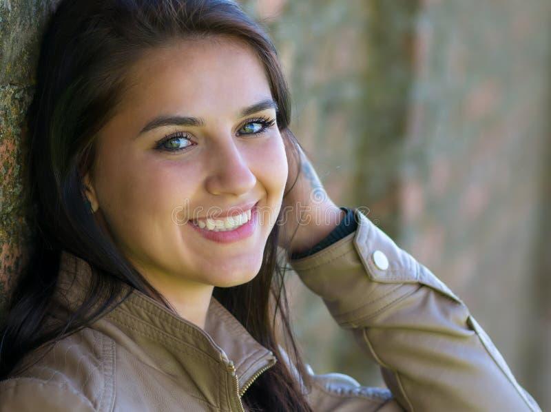 Stående av le, härlig benägenhet för ung kvinna mot en vägg royaltyfria foton