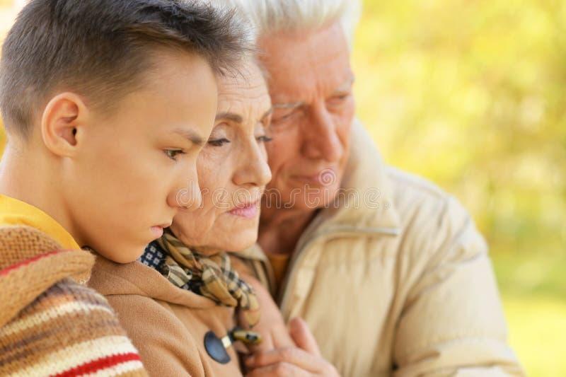 Stående av ledset krama för farfar, för farmor och för sonson royaltyfri bild