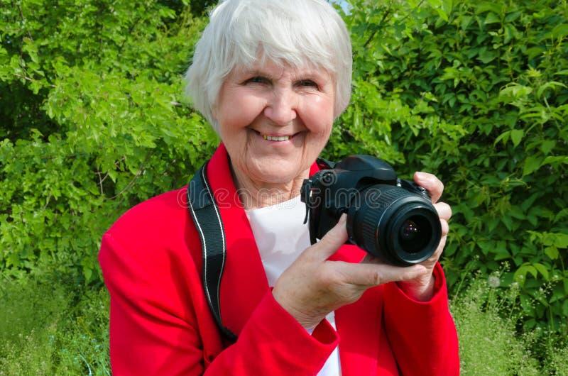 St?ende av leendet, lycklig farmor att tycka om hennes hobby p? soldagen den moderna farmodern ?r den yrkesm?ssiga fotografen arkivfoto
