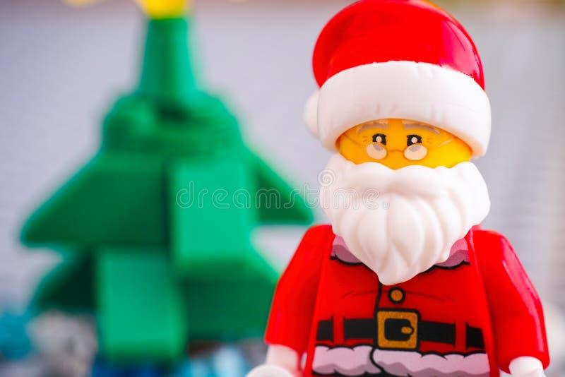 Stående av Lego Santa Claus mot julgranen arkivfoto