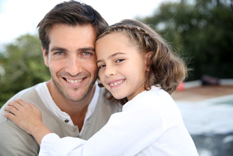 Stående av lilla flickan i armarna av henne fader arkivbild