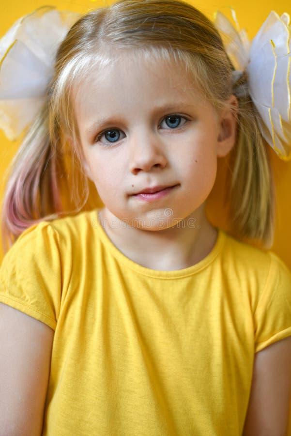 St?ende av lilla flickan i en gul kl?nning p? en gul bakgrund arkivfoto