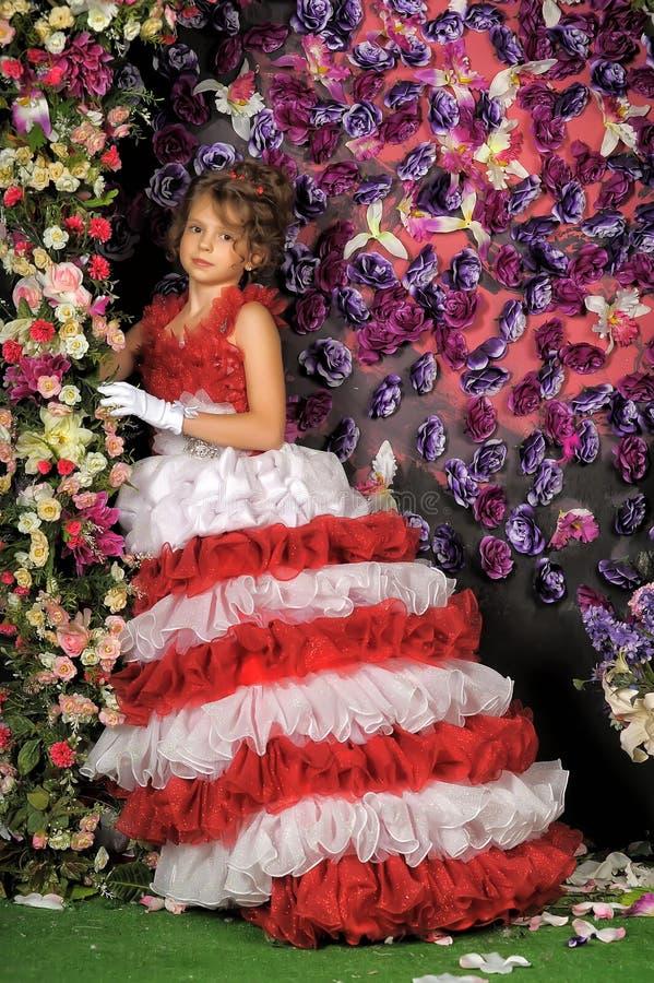 Stående av lilla flickan i klänning med blomman arkivfoton