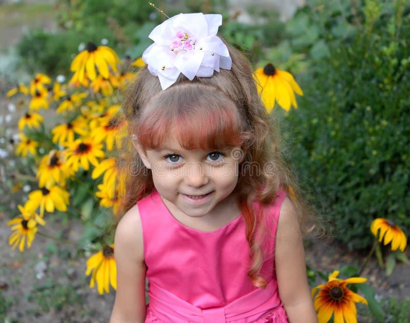 Stående av lilla flickan mot bakgrunden av de blomstra coneflowersna arkivfoton