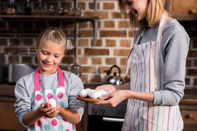 stående av lilla flickan och modern i förkläden som rymmer rå fega ägg medan arkivfoto