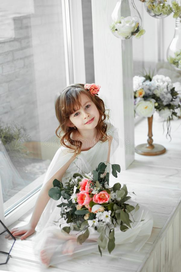 Stående av lilla flickan som sitiing på den vita träfönster-fönsterbrädan med det stora ljusa fönstret arkivfoton