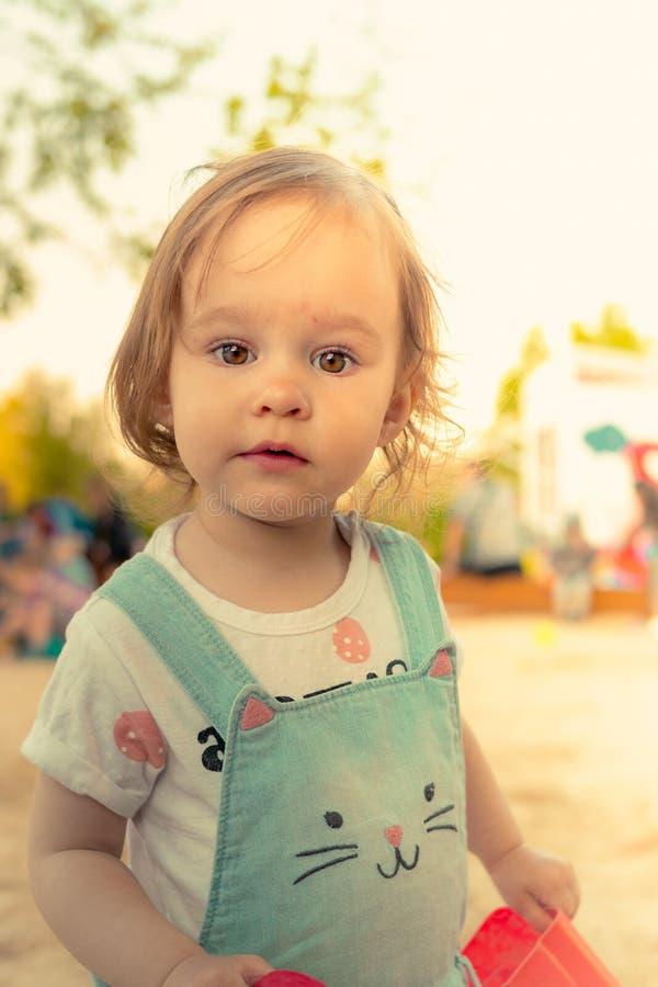 Stående av lilla flickan som spelar i sommar med sand i sandlåda royaltyfri fotografi