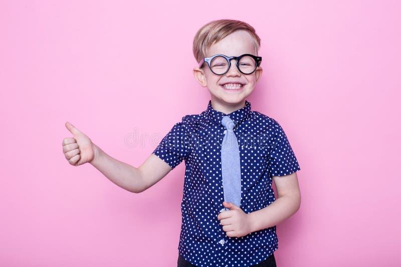 Stående av lite att le pojken i roligt exponeringsglas och band skola förträning Mode Studiostående över rosa bakgrund arkivfoto