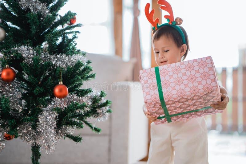 Stående av lite bärande julgåva för dotter royaltyfri foto
