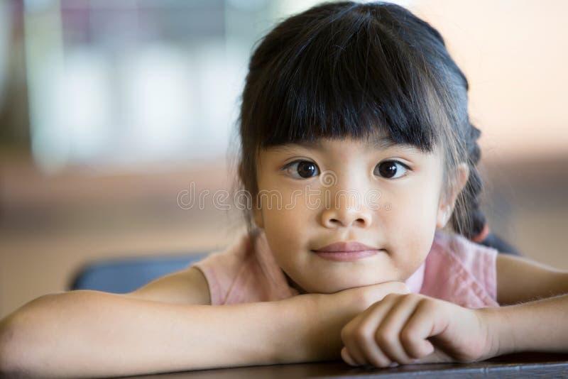 Stående av lite den asiatiska barnflickan som ser kameran arkivfoton