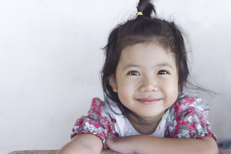 Stående av lite den asiatiska flickan, medan le i gulliga röda dres arkivfoton