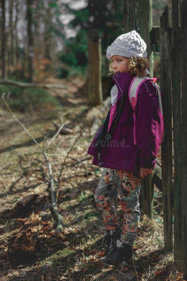 Stående av lite den caucasian flickan i ett iklätt skogbarn ett omslag och en hatt, stor suddighetsbakgrund royaltyfri fotografi