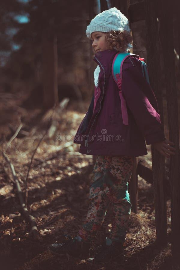 Stående av lite den caucasian flickan i ett iklätt skogbarn ett omslag och en hatt, stor suddighetsbakgrund royaltyfri bild