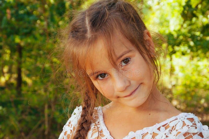 Stående av lite den förtjusande lilla flickan som ler, i fält med gula blommor royaltyfri fotografi