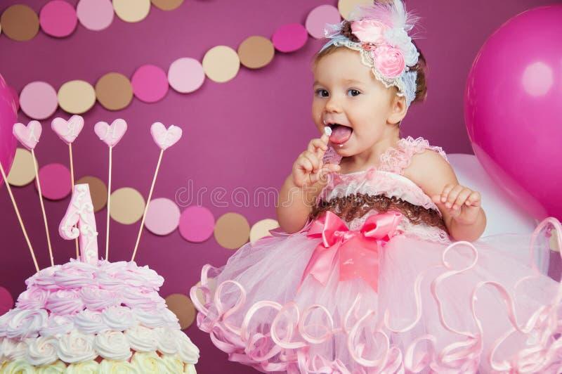 Stående av lite den gladlynta födelsedagflickan med den första kakan Äta den första kakan Dundersuccékaka arkivbild