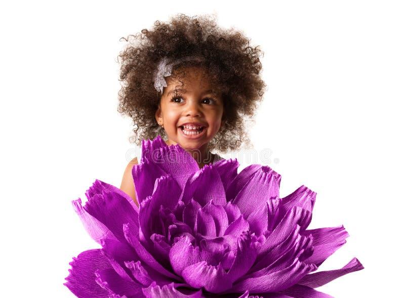 Stående av lite den gulliga flickan med stor purpurfärgad blommaorigami som isoleras royaltyfri foto