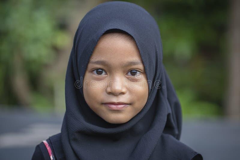 Stående av lite den indonesiska muslimflickan på gatorna i Ubud, ö Bali, Indonesien, slut upp royaltyfria bilder