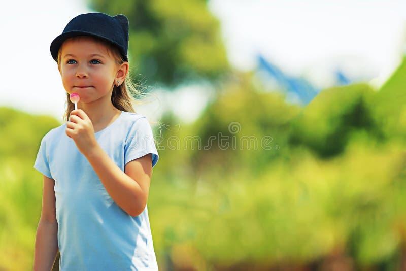Stående av lite den karismatiska flickan liten flicka i en huvudbonad Flicka med godisen konst som retuscherar fotoet royaltyfria foton