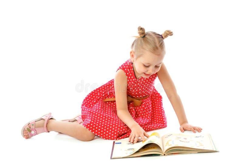 Stående av lite flickaläseböcker som sitter på golvet arkivfoto