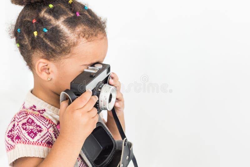 Stående av lite flickan i en färgrik klänning som tar bilder på en gammal tappningkamera arkivfoto