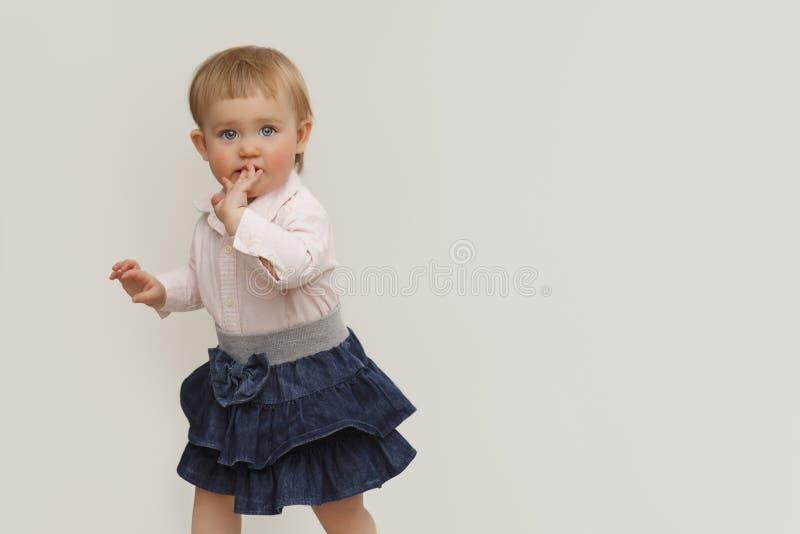 Stående av lite flickan med blåa ögon på en vit bakgrund royaltyfri foto