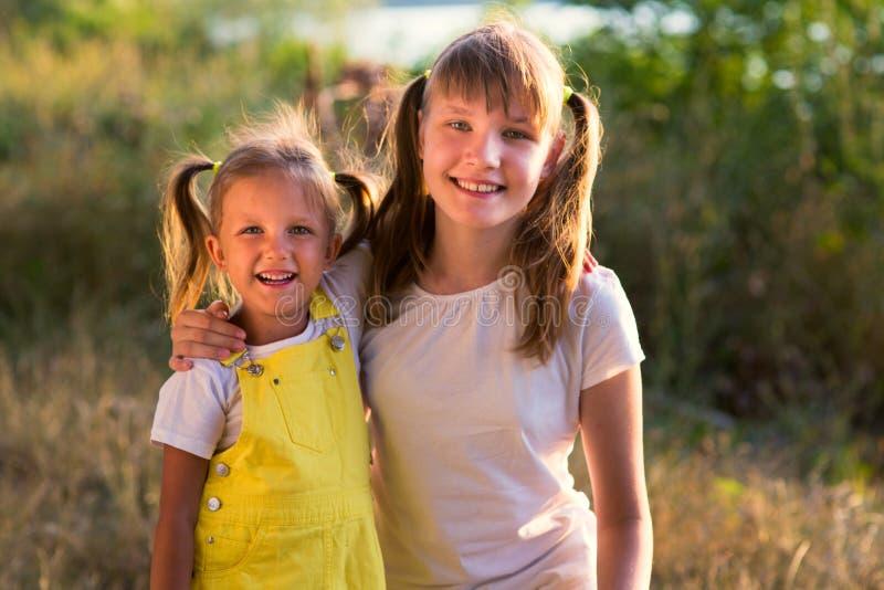 Stående av lite flickan med den äldre systern som är tonårig i natur arkivbild