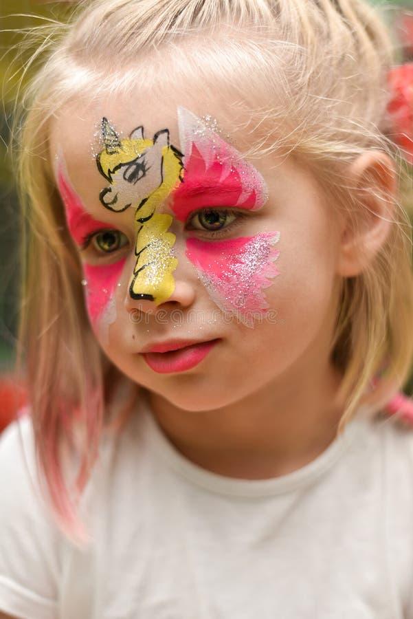 Stående av lite flickan med en enhörningmodell på hennes framsida royaltyfria foton