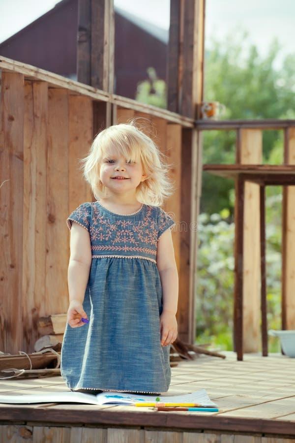 Stående av lite flickan som är stolt av hennes teckning royaltyfri fotografi