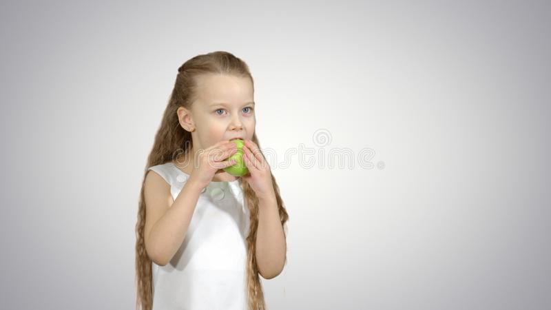 Stående av lite flickan som äter det gröna äpplet på vit bakgrund royaltyfria foton