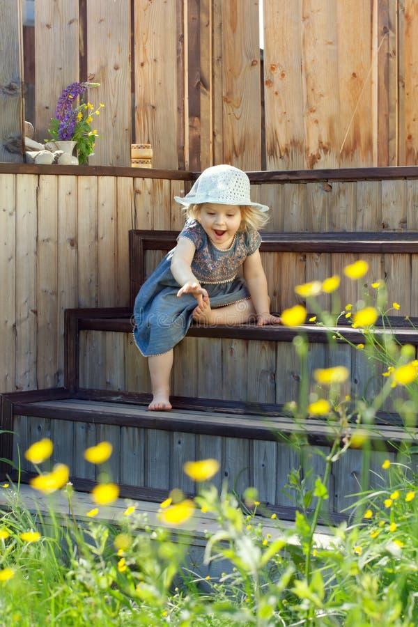 Stående av lite flickan som försöker till för något, utomhus- natur royaltyfri bild