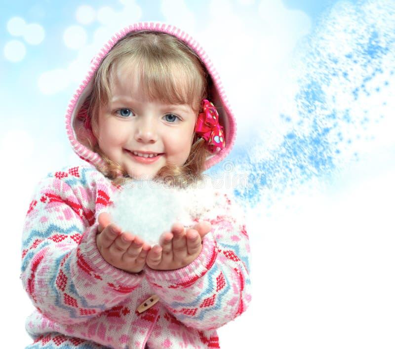 Stående av lite flickan som rymmer en snö arkivbilder