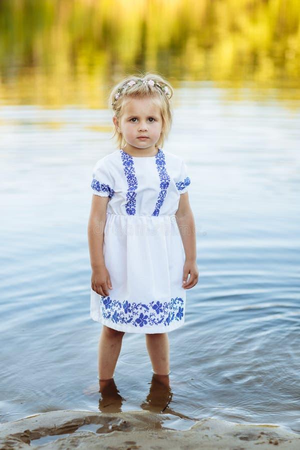 Stående av lite flickan som står i vatten i en vit klänning sommar f?r berg f?r strandkustlinjehorisont royaltyfri foto