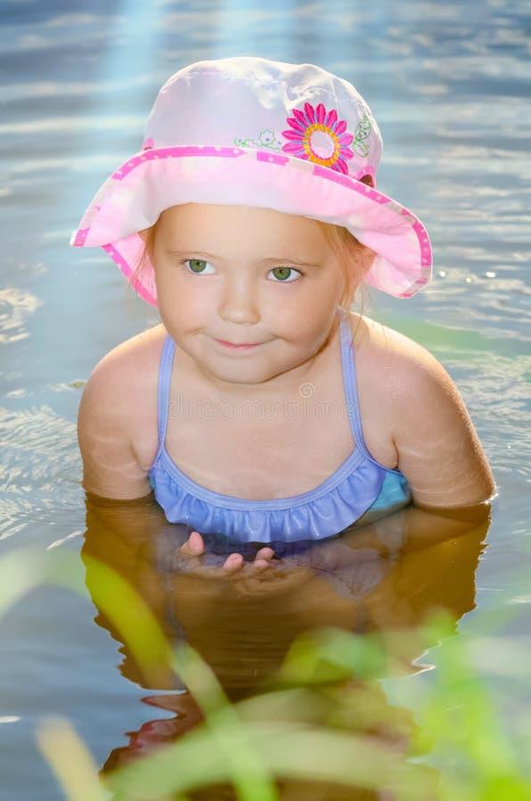 Stående av lite flickasammanträde i vattnet arkivbilder