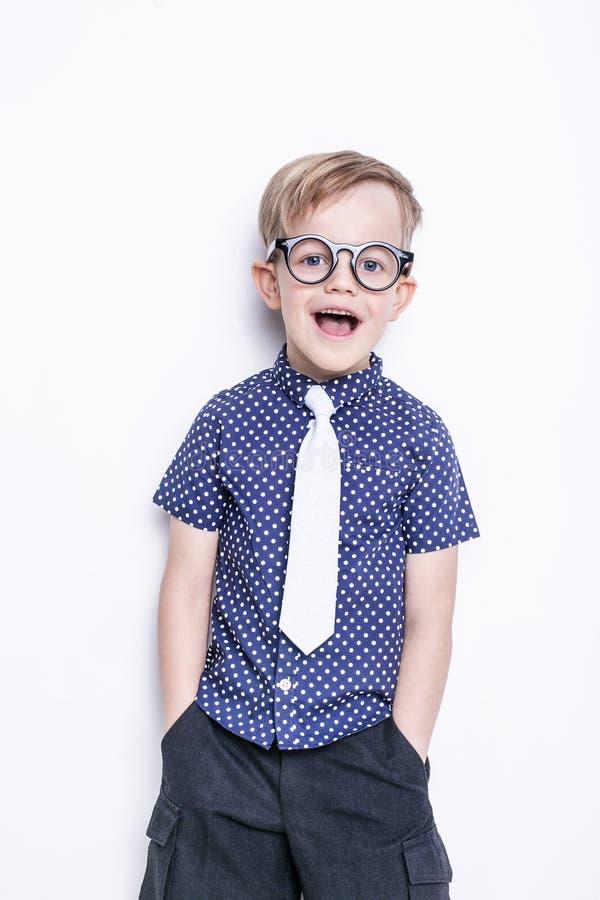 Stående av lite pojken i roligt exponeringsglas och band skola förträning Mode Studiostående som isoleras över vit bakgrund royaltyfri fotografi