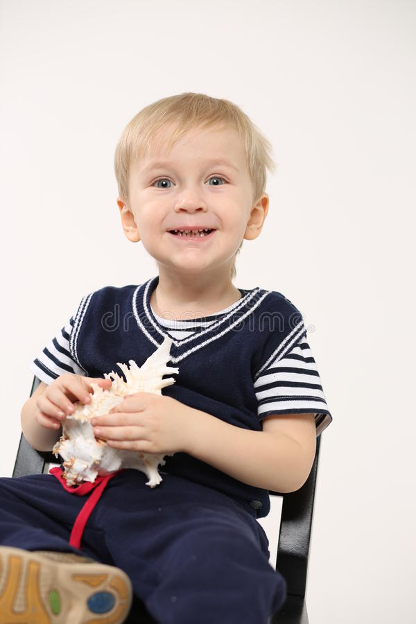 Stående av lite pojken med ett snäckskal i hans händer, ljus bakgrund arkivbild