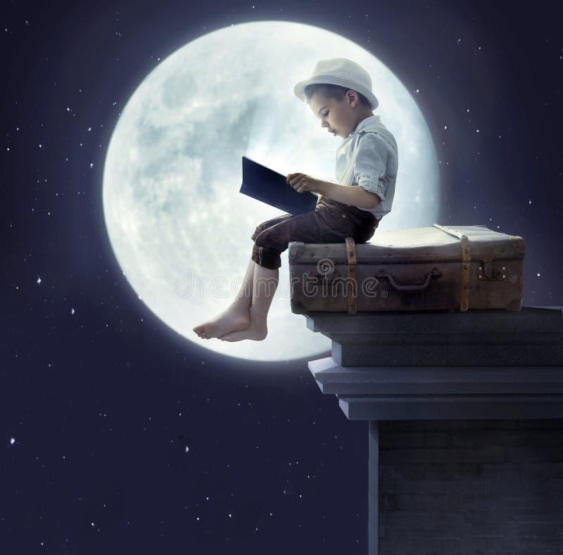 Stående av lite pojken som läser en bok royaltyfri foto