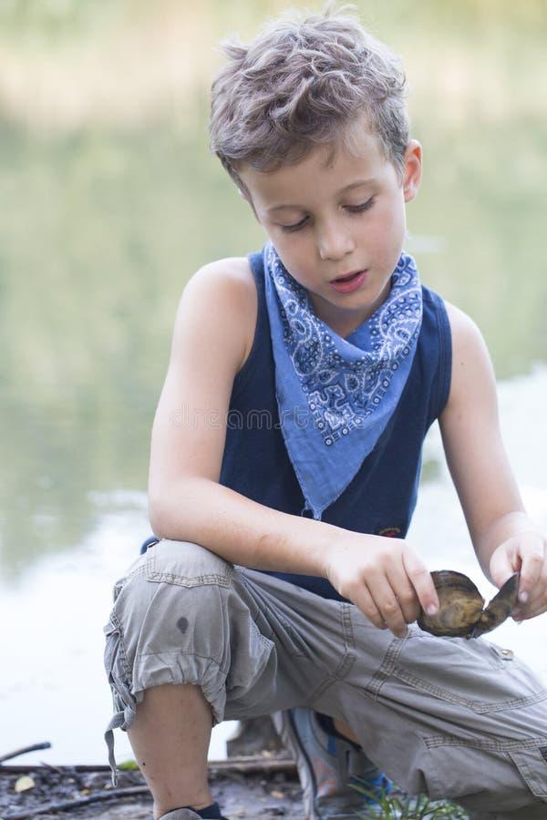 Stående av lite sött pojkesammanträde på floden och collectien arkivbild