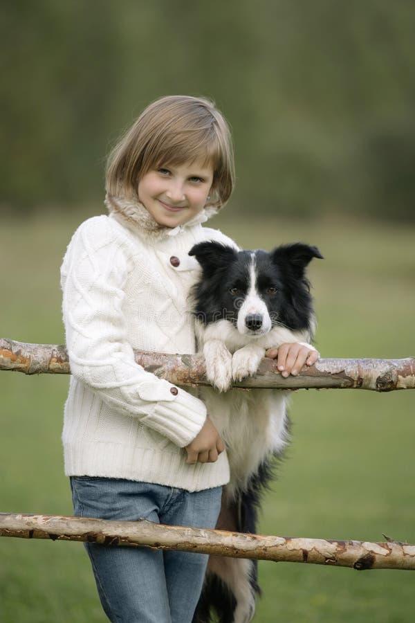 Stående av lite unga flickan som står och krama hunden livsstil arkivbilder