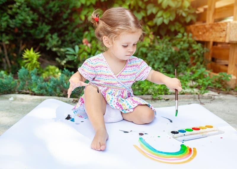 Stående av liten blond flickamålning, utomhus- sommar arkivbild