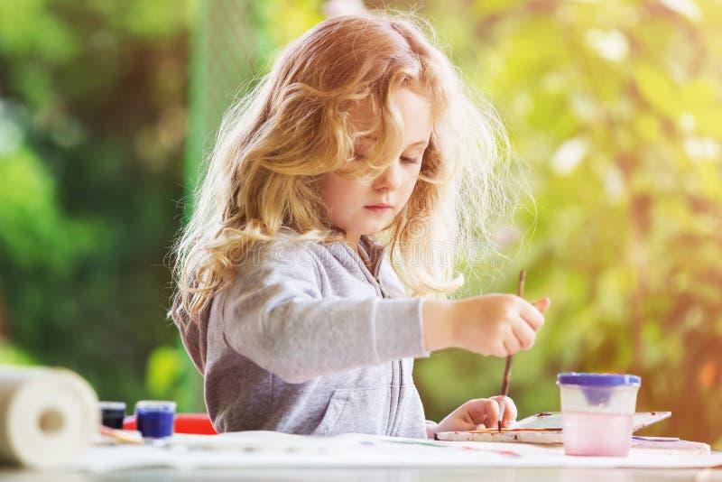 Stående av liten blond flickamålning, utomhus- sommar arkivfoton