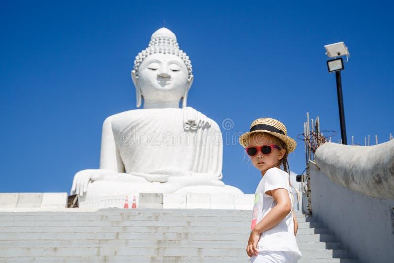 Stående av liten flickaanseendet nära den stora Buddhastatyn i Phuket, Thailand Begrepp av turism i Asien och berömt fotografering för bildbyråer