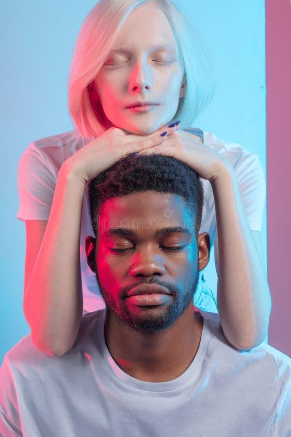 Stående av lugna härliga par för blandat lopp med stängda ögon meditation arkivbilder