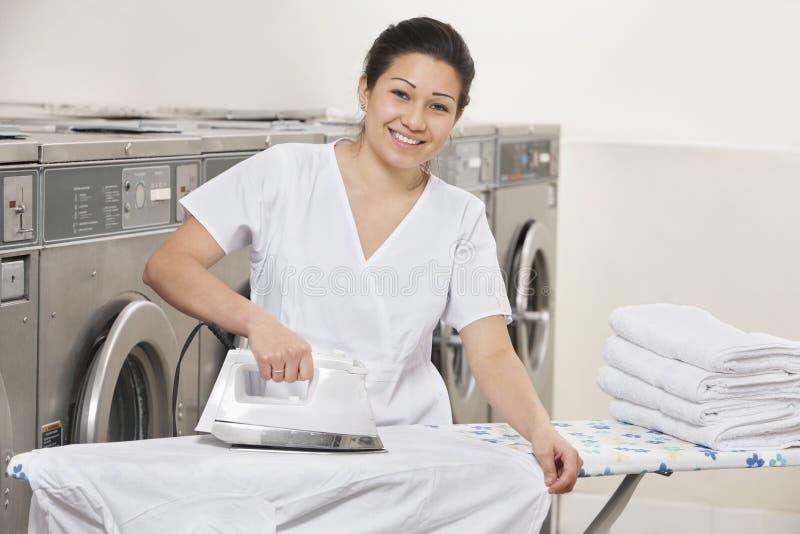 Stående av lycklig kläder för en strykning för ung kvinna i tvättinrättning royaltyfri foto